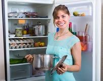 Mujer sonriente cerca del refrigerador lleno Imagen de archivo libre de regalías