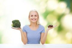 Mujer sonriente con bróculi y el buñuelo Foto de archivo libre de regalías