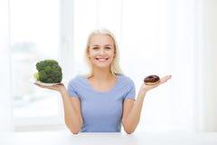 Mujer sonriente con bróculi y el buñuelo en casa Imagen de archivo