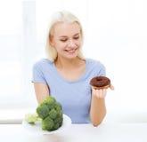 Mujer sonriente con bróculi y el buñuelo en casa Fotos de archivo