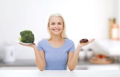 Mujer sonriente con bróculi y el buñuelo en cocina Imagenes de archivo