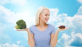 Mujer sonriente con bróculi y el buñuelo sobre el cielo Fotografía de archivo