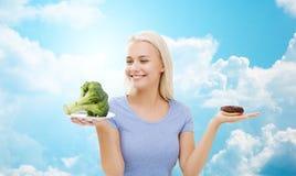 Mujer sonriente con bróculi y el buñuelo sobre el cielo Foto de archivo