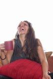 Mujer sonriente con café en el sofá foto de archivo