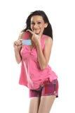 Mujer sonriente con de la tarjeta de crédito azul Foto de archivo libre de regalías
