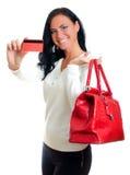 Mujer sonriente con de la tarjeta de crédito rojo Foto de archivo libre de regalías