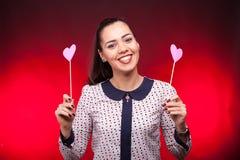 Mujer sonriente con dos corazones rosados Imagen de archivo libre de regalías