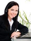 Mujer sonriente con el auricular en oficina Fotos de archivo libres de regalías