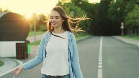 Mujer sonriente con el bolso de compras que camina en la calle en el parque de la ciudad Mujer feliz almacen de video