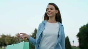 Mujer sonriente con el bolso de compras que camina en parque del verano Mujer feliz metrajes