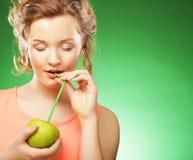 Mujer sonriente con el cóctel de la manzana y de la paja, sobre backgro verde Imagenes de archivo