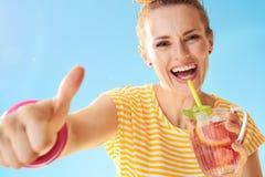 Mujer sonriente con el cóctel de restauración que muestra los pulgares para arriba fotografía de archivo libre de regalías