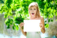 Mujer sonriente con el cartel en blanco al aire libre Foto de archivo