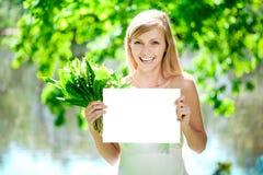 Mujer sonriente con el cartel en blanco al aire libre Foto de archivo libre de regalías