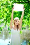 Mujer sonriente con el cartel en blanco al aire libre Fotografía de archivo