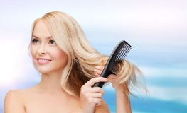 Mujer sonriente con el cepillo de pelo Imagen de archivo libre de regalías