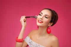 Mujer sonriente con el cepillo del maquillaje Ella se está colocando foto de archivo