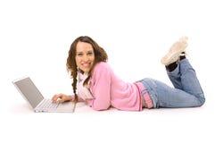 Mujer sonriente con el cuaderno que miente en el suelo Imagenes de archivo