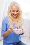 Mujer sonriente con el cuenco de muesli que desayuna Foto de archivo libre de regalías