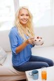 Mujer sonriente con el cuenco de muesli que desayuna Fotografía de archivo