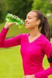 Mujer sonriente con el jugador que bebe de la botella Fotografía de archivo