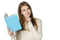 Mujer sonriente con el libro abierto que mira a la cara Fotos de archivo libres de regalías