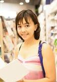 Mujer sonriente con el libro en manos en una librería fotografía de archivo