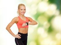 Mujer sonriente con el monitor del ritmo cardíaco a mano Fotografía de archivo