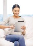 Mujer sonriente con el ordenador de la PC de la tableta en casa Foto de archivo libre de regalías