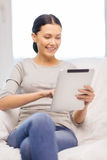 Mujer sonriente con el ordenador de la PC de la tableta en casa Imágenes de archivo libres de regalías