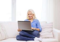 Mujer sonriente con el ordenador portátil en casa Fotos de archivo