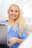 Mujer sonriente con el ordenador portátil en casa Fotos de archivo libres de regalías