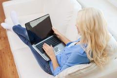 Mujer sonriente con el ordenador portátil en casa Foto de archivo libre de regalías