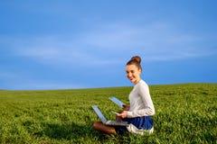 Mujer sonriente con el ordenador portátil, la tableta y el teléfono Imagen de archivo libre de regalías