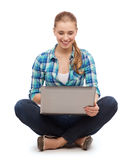 Mujer sonriente con el ordenador portátil que se sienta en piso Fotografía de archivo libre de regalías