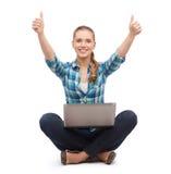 Mujer sonriente con el ordenador portátil y el mostrar los pulgares para arriba Imagen de archivo libre de regalías