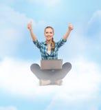 Mujer sonriente con el ordenador portátil y el mostrar los pulgares para arriba Imágenes de archivo libres de regalías
