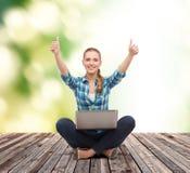 Mujer sonriente con el ordenador portátil y el mostrar los pulgares para arriba Fotos de archivo