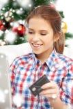 Mujer sonriente con el ordenador portátil y la tarjeta de crédito Fotografía de archivo