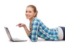Mujer sonriente con el ordenador portátil y señalar el finger Fotografía de archivo libre de regalías