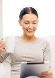 Mujer sonriente con el ordenador y la taza de la PC de la tableta Imagen de archivo