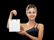 Mujer sonriente con el panier en blanco blanco Foto de archivo libre de regalías