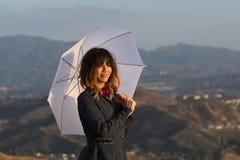 Mujer sonriente con el paraguas blanco en la puesta del sol Fotografía de archivo