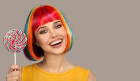 mujer sonriente con el pelo colorido brillante que sostiene la piruleta grande imágenes de archivo libres de regalías