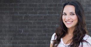 Mujer sonriente con el pelo marrón contra la pared fotografía de archivo