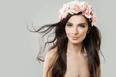 Mujer sonriente con el pelo y Rose Flowers que soplan Foto de archivo