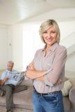 Mujer sonriente con el periódico de la lectura del hombre en casa fotos de archivo