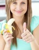 Mujer sonriente con el pulgar encima de sostener un plátano Imagenes de archivo