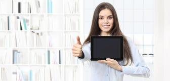 Mujer sonriente con el pulgar similar para arriba que muestra la tableta digital en libra Fotografía de archivo libre de regalías