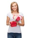 Mujer sonriente con el ramo de flores y de caja de regalo Imagen de archivo